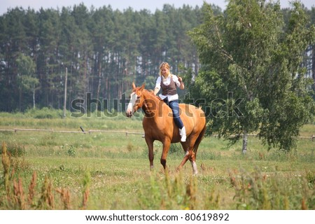 Beautiful blonde woman riding chestnut horse without saddle and bridle