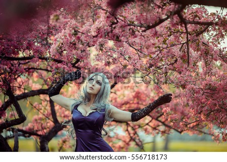 Beautiful blonde woman walking in spring garden under blooming trees. Spring gothic fashion. Cute flower scene