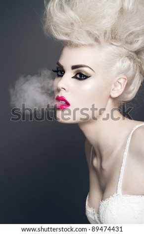 Beautiful blonde woman with professional make-up and smoke coming out of her mouth.