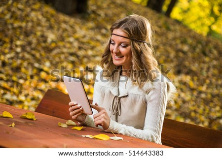 Beautiful boho girl enjoys using digital tablet in the park.Boho girl using digital tablet