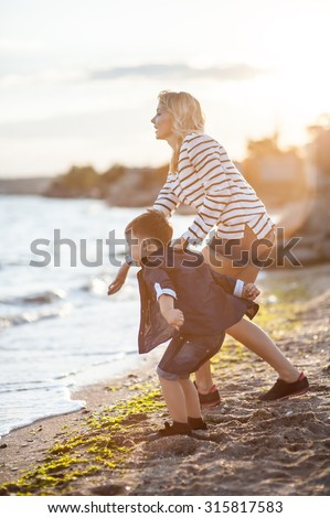 Beautiful boy with a woman relaxing on the beach. Throw pebbles into the sea, running, jumping, laughing and having a great time with each other at sunset.