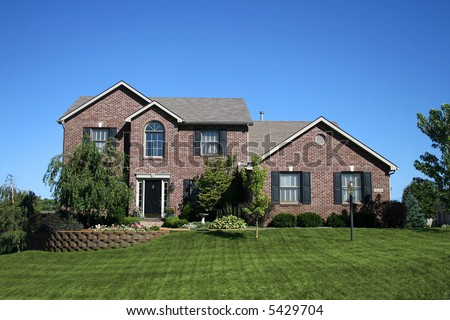 Yellow victorianstyle house green roof blue stock photo for Beautiful two story homes