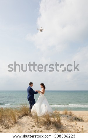 Beautiful bride and groom at the beach with drone