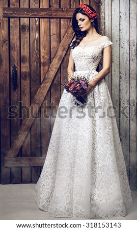Beautiful bride. girl with wreath of red berries and pigtail .