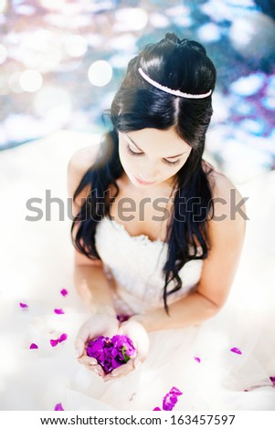 beautiful bride holding rose petals in the shape of a heart