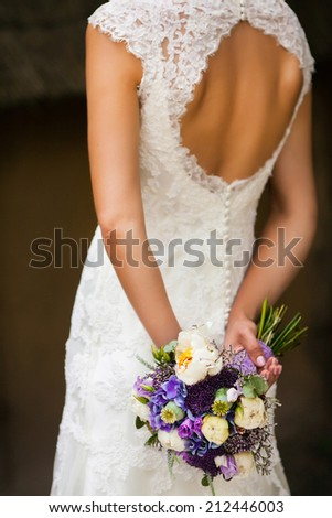 Beautiful bride in a white dress with a bouquet of flowers in he