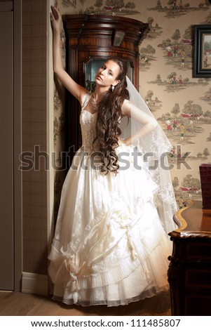 Beautiful bride in elegant wedding dress with long curly hair