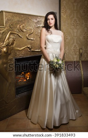 Beautiful bride in white wedding dress standing in her boudoir.
