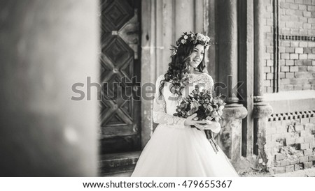 Beautiful bride near old big wooden doors