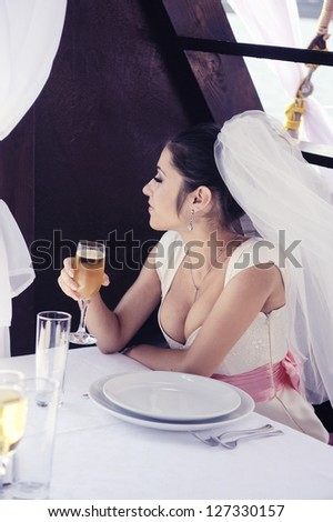 Beautiful bride on the yacht with a glass of champagne.