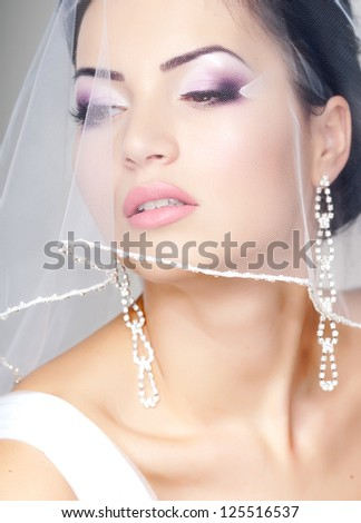 beautiful bride portrait with veil over her face, wearing professional make-up