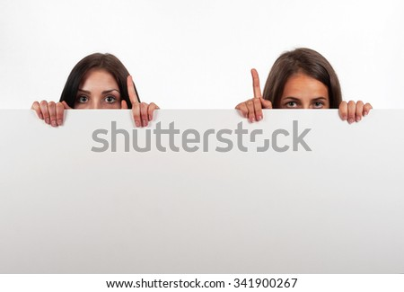 Beautiful brunette and blonde looking  and indicate, on white background