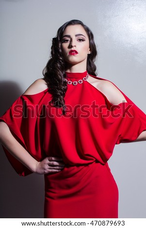 Beautiful brunette beauty model with red dress and hard edgy lighting