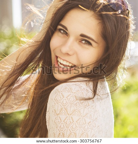 Beautiful brunette caucasian young woman laughing showing perfect teeth on summer sunny day. outdoors. nature