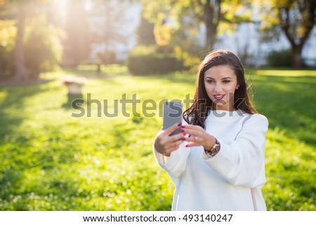 Beautiful brunette girl taking a self portrait in the park at sunset. Very shallow depth of field