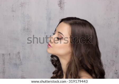 Beautiful brunette holding a brush for applying makeup. Beauty portrait with makeup and hairdo attractive