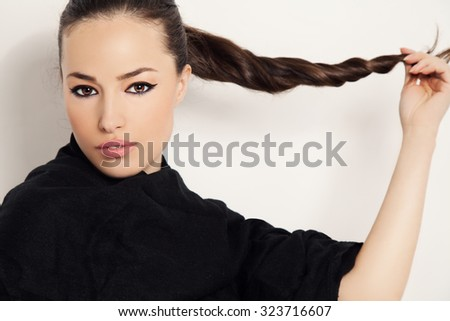 beautiful brunette holds her long ponytail, studio white