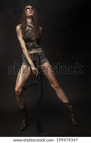 Beautiful brunette model with gun posing in full growth in studio