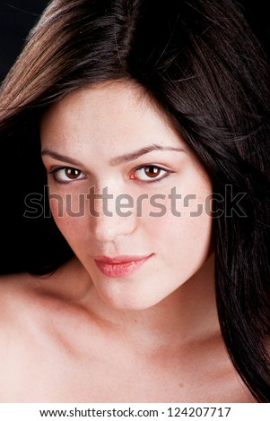 Beautiful brunette with freckles on a black background
