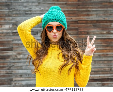 Beautiful brunette woman in sunglasses and knitted  cap blowing lips kiss over wooden background.