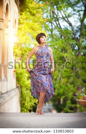 beautiful brunette woman wearing bright dress posing in autumn park. attractive slim caucasian sexy girl with brown hair outdoor. Alluring lady with short hairstyle and professional makeup. series