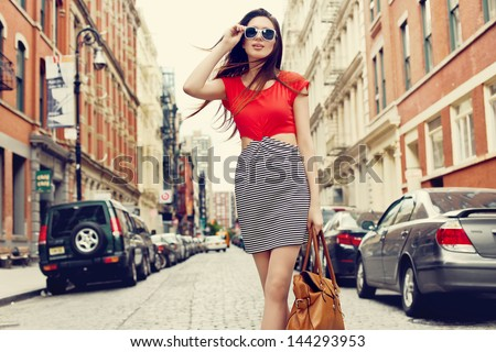 Beautiful brunette young woman wearing dress and walking on the street