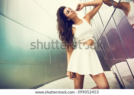 Beautiful brunette young woman wearing fashionable white dress in the city. Fashion photo