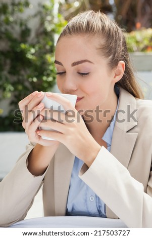 Beautiful businesswoman enjoying a coffee outside at the coffee shop