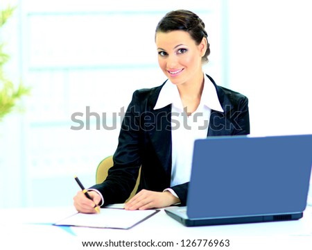 Beautiful businesswoman fills the plan of work in the office.