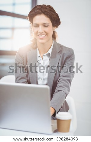 Beautiful businesswoman using laptop at desk in office