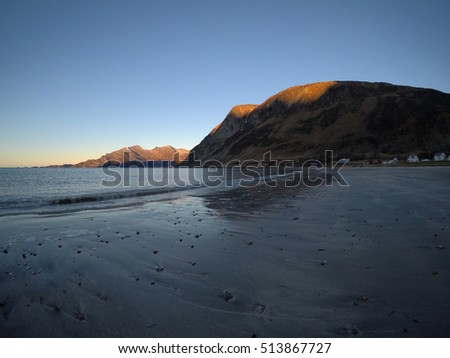 beautiful calm blue waves hitting white frozen sandy beach in late autumn in the arctic circle with deep mountain and open sea view on clear sky with small settlement in background