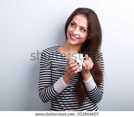 Beautiful calm thinking woman drinking coffee from cup on blue background