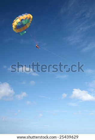 Beautiful Caribbean tropical ocean with two people parasailing, suitable background for a variety of designs