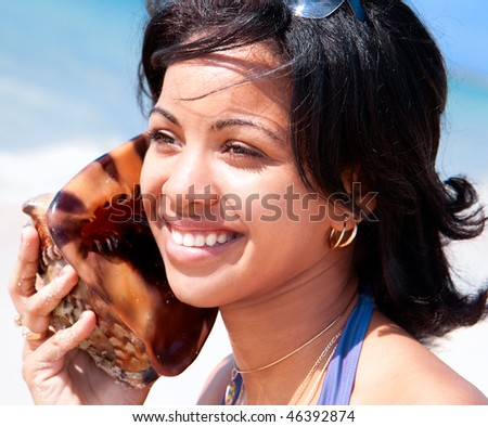 Beautiful caribbean woman holding a conch shell to her ears