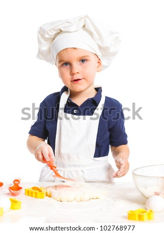 Beautiful caucasian boy making a cake, smiling happily, isolated on white background