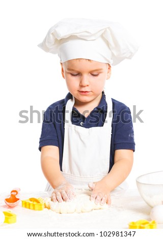 Beautiful caucasian boy making a cake, smiling happily, isolated on white background. Vertical view