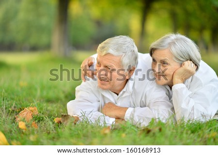Beautiful Caucasian elderly couple lying on grass