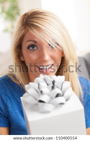 Living room wearing a blue shirt holding a white gift with a big