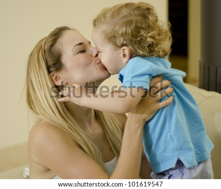 Beautiful caucasian mother kissing her cute son