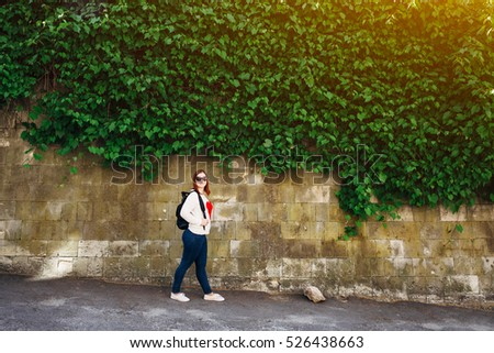 Beautiful cheerful girl in sweater with red heart walking in city. Sunny summer day. Looking at camera