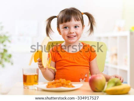 Beautiful child girl eating healthy food fruits at home