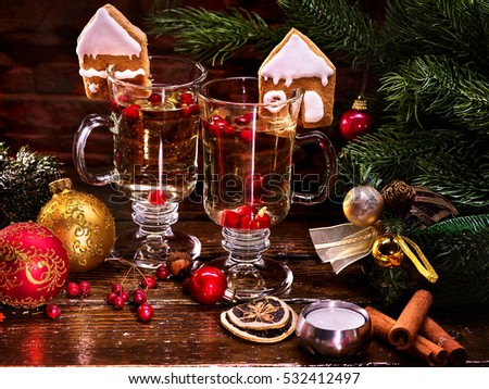 Beautiful Christmas still life with two glasses of hot punch and Christmas balls. In background Christmas tree, candle.