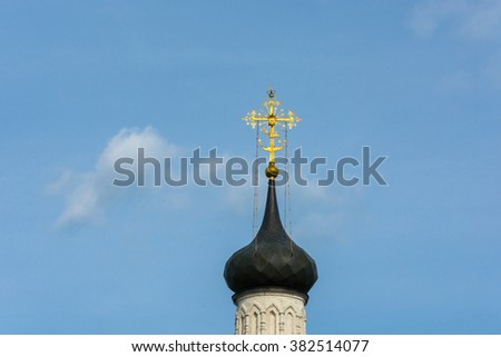 Beautiful Church dome with a Golden cross against the cloudy sky.