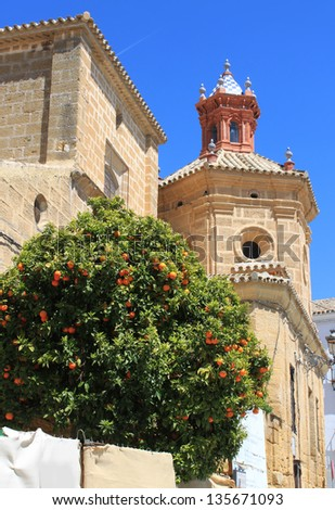 Beautiful church steeple displaying Moorish architecture with orange tree in Osuna, Andalusia, Spain