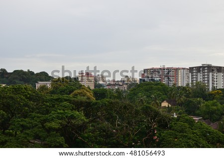 Beautiful coastal green city of Mangalore, in Karnataka State, India. A mixture of traditional tile roof houses and concrete multi-story buildings are surrounded by coconut palms and trees