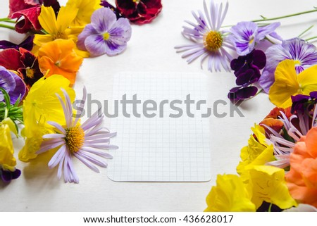 Beautiful colorful flowers and an open notebook the white background
