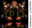 Beautiful colorful 2013 new year fireworks on the black sky background with reflection in water, long exposure - stock photo