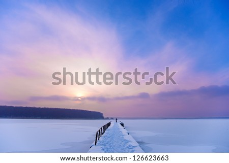 Beautiful Colorful Sunset over Frozen River and Pier