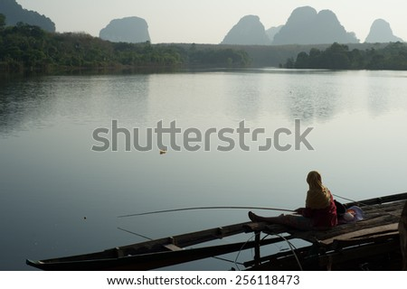Beautiful colors of the sky,water reflection and Angler during sunrise at Ban Nong Thale Krabi Province in Thailand