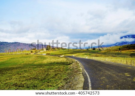 Beautiful countryside landscape with road and meadows after rain